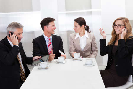 Business executives sitting around a table enjoying a relaxing cup of coffee together during a break photo
