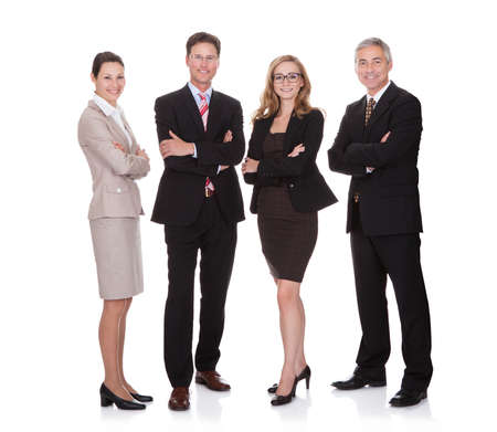 business men: Successful business team with two attractive businesswoman and two middle-aged businessmen standing in a row smiling at the camera