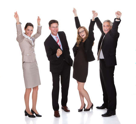 Four excited diverse professional businesspeople celebrating a success laughing and raising their arms in the air isolated on white Stock Photo - 17260767