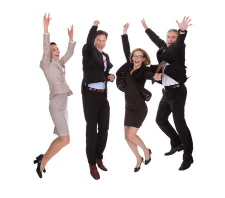 motivated: Four diverse professional business partners jumping for joy with their arms raised shouting in jubilation isolated on white Stock Photo
