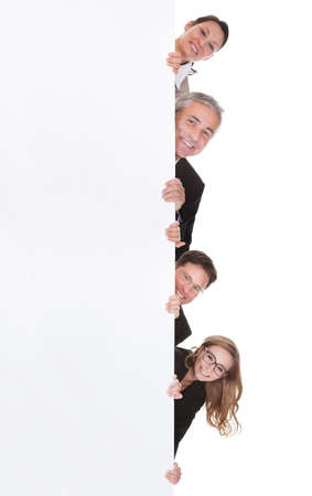 Four diverse professional businesspeople peering around the edge of a tall blank white banner with copyspace isolated on white Stock Photo - 17260998