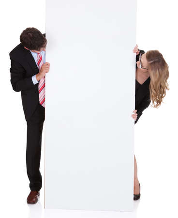 Smiling professional man and woman wearing glasses holding up a blank white sign for your text or advertisement isolated on white Stock Photo - 17260776