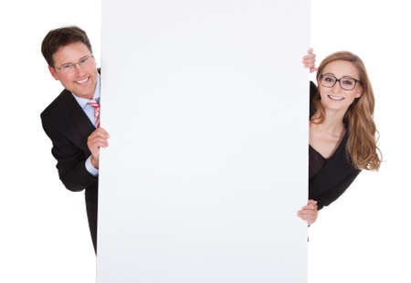 Smiling professional man and woman wearing glasses holding up a blank white sign for your text or advertisement isolated on white Stock Photo - 17260780
