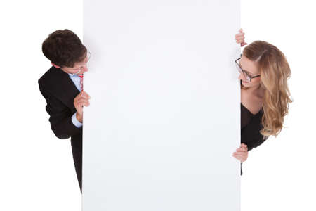 Smiling professional man and woman wearing glasses holding up a blank white sign for your text or advertisement isolated on white Stock Photo - 17260790