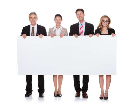 holding blank sign: Four diverse professional businesspeople holding a blank banner or horizontal sign for your text or advertisement isolated on white