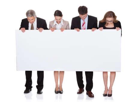 Cuatro empresarios profesional diversa, con un cartel en blanco o signo horizontal para el texto o un anuncio aislado en blanco Foto de archivo - 17260773