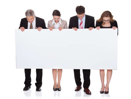 Four diverse professional businesspeople holding a blank banner or horizontal sign for your text or advertisement isolated on white