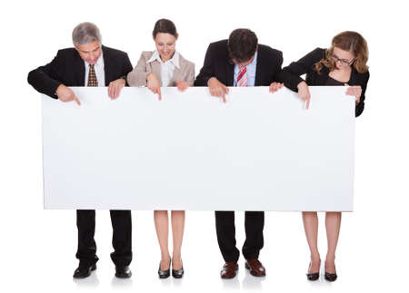 look down: Four diverse professional businesspeople holding a blank banner or horizontal sign for your text or advertisement isolated on white