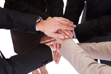 Group of four diverse businesspeople standing in a circle facing each other holding hands in a team Stock Photo - 17276945