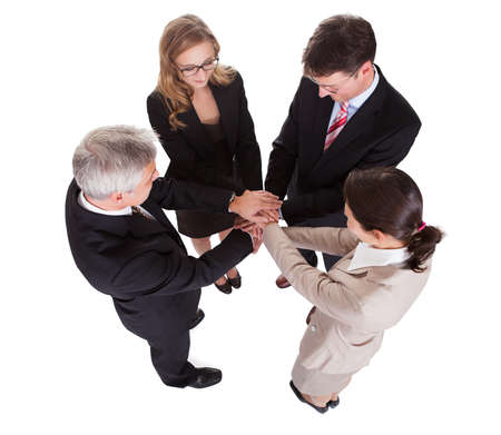 Group of four diverse businesspeople standing in a circle facing each other holding hands in a team Stock Photo - 17260814