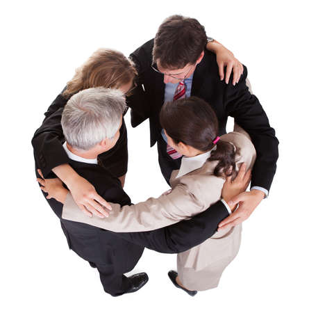 Group of four diverse businesspeople standing in a circle facing each other holding hands in a team Stock Photo - 17260845