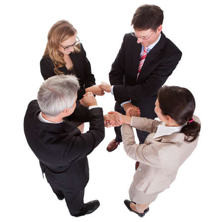 Group of four diverse businesspeople standing in a circle facing each other holding hands in a team Stock Photo - 17260796