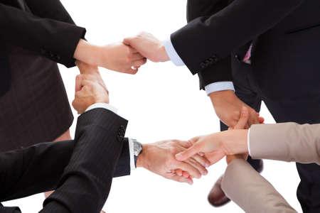 pacto: Recortada vista aérea de un grupo diverso de hombres de negocios que une las manos en un equipo