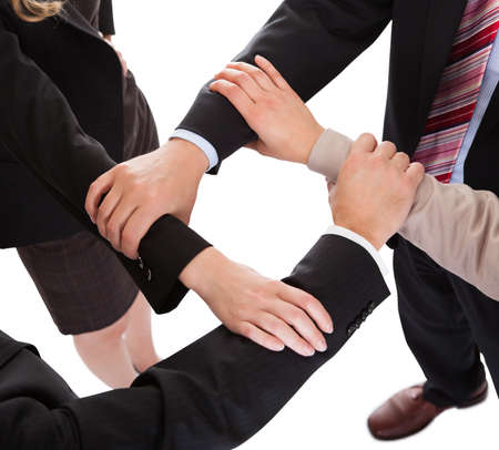 linked: Cropped overhead view of a diverse group of businesspeople linking hands in a team