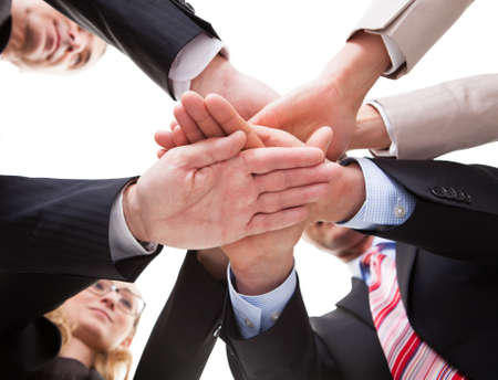 View from underneath of a group of businesspeople standing in a circle placing their hands on top of each other Stock Photo - 17260924