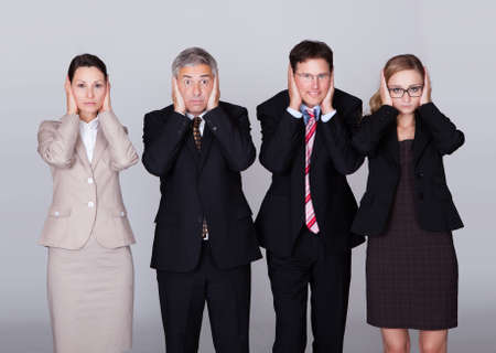 verbal communication: Four diverse businesspeople standing in a row holding their ears in a conceptual representation of the saying - Hear no evil
