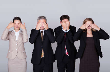 Four diverse businesspeople standing in a row holding their eyes shut in a conceptual representation of the saying - See no evil