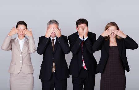 escuchar: Cuatro empresarios diverso de pie en una fila manteniendo sus ojos cerrados en una representaci�n conceptual de la frase - See no evil Foto de archivo