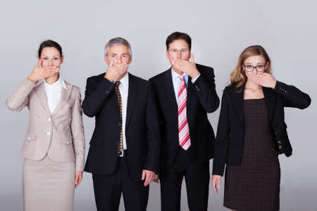 Four diverse businesspeople standing in a row gesturing for silence in a conceptual representation of the saying - Speak no evil