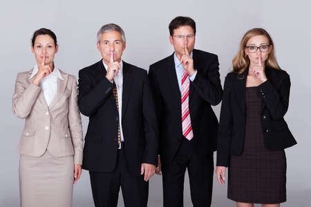 Four diverse businesspeople standing in a row gesturing for silence in a conceptual representation of the saying - Speak no evil photo