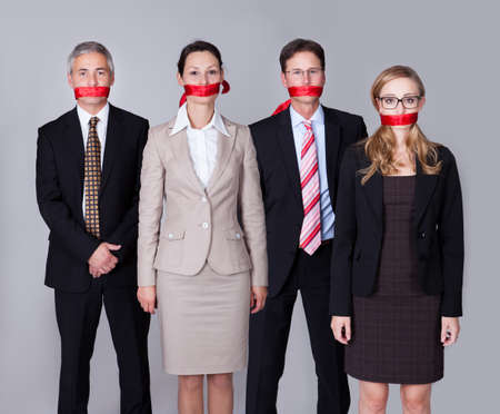 sellotape: Businesspeople bound by red tape around their mouths standing in a row unable to speak or divulge information Stock Photo