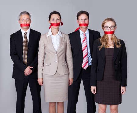 mouth closed: Empresarios vinculados por una cinta roja alrededor de la boca de pie en una fila no puede hablar o divulgar informaci�n Foto de archivo