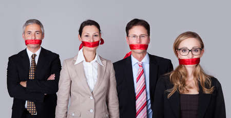 unable: Businesspeople bound by red tape around their mouths standing in a row unable to speak or divulge information Stock Photo
