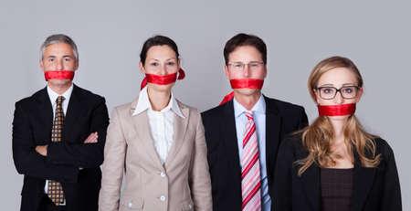 silencio: Empresarios vinculados por una cinta roja alrededor de la boca de pie en una fila no puede hablar o divulgar informaci�n Foto de archivo