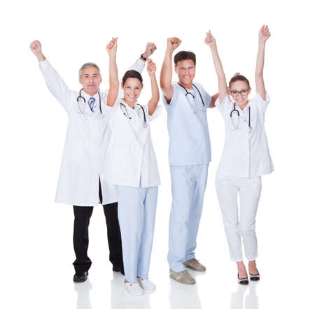 outcome: Diverse medical team of male and female doctors and nurses celebrating a successful outcome to a case