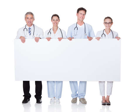 Four attractive professional diverse medical staff holding up a long horizontal blank white banner for your text or advertisement photo