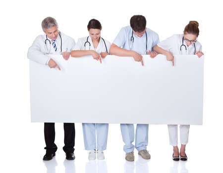 Four attractive professional diverse medical staff holding up a long horizontal blank white banner for your text or advertisement Stock Photo