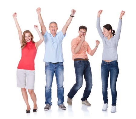 diverse group of people: Two happy attractive couples in casual clothes and jeans celebrating raising their arms in the air and shouting on white