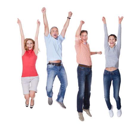 saltando: Dos parejas felices en la ropa ocasional que salta en el aire alegr�a con los brazos en alto aislados en blanco