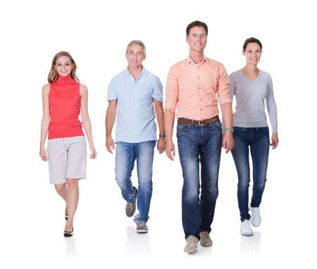 personas caminando: Grupo de cuatro personas caminando hacia la cámara. Aislado en blanco