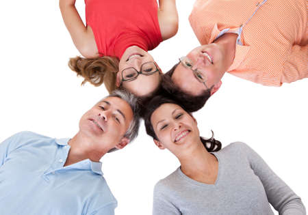 inwards: Conceptual image of four smiling middle-aged friends facing inwards with their heads together looking down at the camera isolated on white