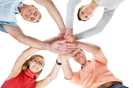 Conceptual teamwork and cooperation image of four casual middle-aged friends isolated on white Stock Photo - 17260925