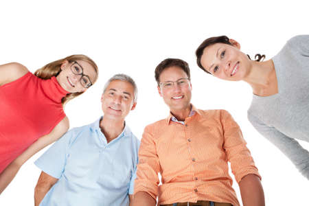 two couples: Two happy attractive middle aged couples standing arm in arm looking down at the camera Stock Photo