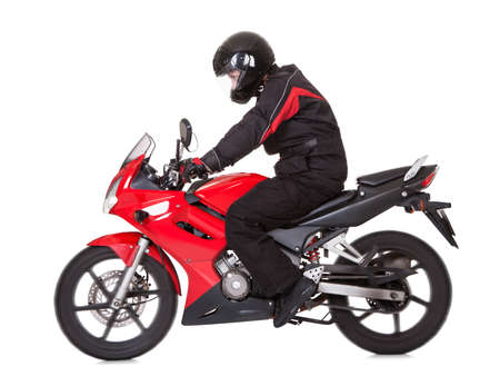 Side view of a young male biker wearing a helmet and gloves riding a red motorbike photo