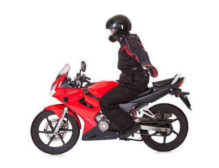 stunts: Biker in protective gear wearing a helmet standing up while riding his red motorbike isolated on white with wheel motion blur Stock Photo