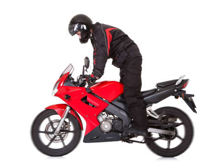 parked bicycles: Biker in protective gear wearing a helmet standing up while riding his red motorbike isolated on white with wheel motion blur Stock Photo