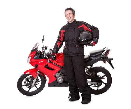 Glimlachende jonge man in beschermende uitrusting met een helm onder zijn arm met zijn rode motor op een witte achtergrond studio