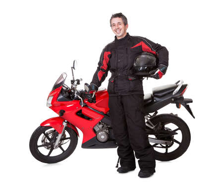 jinete: Hombre joven sonriente en traje protector que sostiene un casco bajo el brazo con su moto roja sobre un fondo blanco de estudio