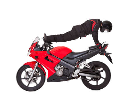 facing backwards: Stunt driver take up a horizontal position facing backwards on his red and black motorcycle. Studio shot isolated on white