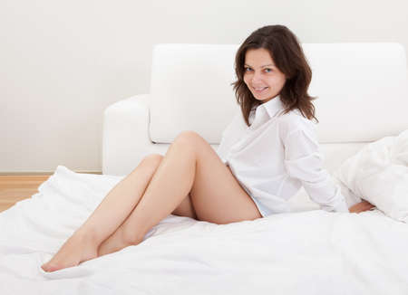 Beautiful natural woman with a gentle smile sitting on her bed with her knees clasped in her arms Stock Photo - 17260786