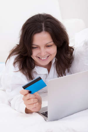 Excited attractive young woman lying on her bed with her laptop making purchases online with her credit card Stock Photo - 17260906