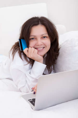Excited attractive young woman lying on her bed with her laptop making purchases online with her credit card Stock Photo - 17260952