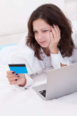 Excited attractive young woman lying on her bed with her laptop making purchases online with her credit card Stock Photo - 17260879