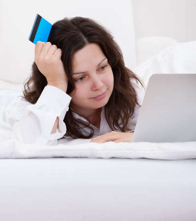 Excited attractive young woman lying on her bed with her laptop making purchases online with her credit card Stock Photo - 17260794