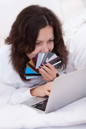Woman with a fistful of credit cards lying on her bed with her laptop browsing online for something to purchase Stock Photo - 17260900