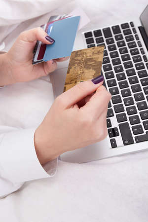 Woman banking or shopping online holding her credit card ready to enter the details on her computer keyboard Stock Photo - 17260802